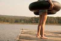 Caucasian girls with inner tubes on wooden dock