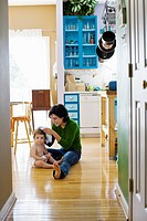 Hispanic mother with toddler on kitchen floor
