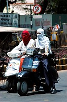 Two wheeler motor bike riders cover their faces with scarf to avoid summer heat at Nagpur , Maharashtra , India