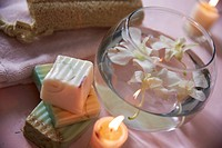 soaps with water bowl of orchids and candle in zen atmosphere