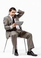 Seated business man looking at tablet
