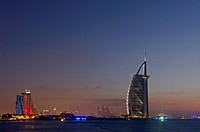 The luxury hotel Burj Al Arab off Jumeirah beach at dusk, the Jumeirah Beach Hotel on the left