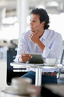 Pensive man with digital tablet at cafe table