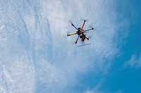 A drone with a camera hovers overhead in the sky.