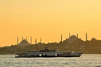 Turkey, Istanbul, View of Ferry Boat on Bosphorus with Blue Mosque at sunset