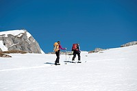 Two skiers moving up a snowy hill on The Dolomites, South Tyrol, Italy