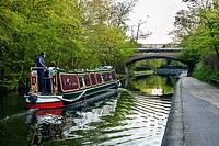 Boat navigating along Regents canal, next to Regents Park, London, UK