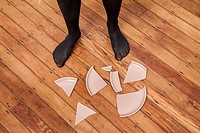 Woman's stocking feet next to a broken plate