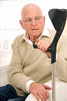 Senior man in a beige pullover, wearing glasses looking puzzled and holding his walking stick