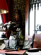 Antique bottles and decanters with paper and in on desk with animal skull in background of residential house, France.