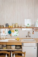 Kitchenware on shelf above sink set in wooden worktop in country style kitchen with wooden walls