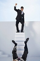 Businessman standing on stairs and other one falling down