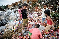 Landfill scavenging. Children searching landfill rubbish for food and materials and items that can be sold on. Photographed on 'Trash moutain', Makass...