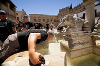Middle-aged man cooling in the fountain gate of Jaen Baeza, Fountain of the lions in the Plaza of Pópulo also called the Lions square, Baeza, Jaén Pro...