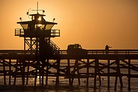 Tourists and surfers at San Clemente Pier at sunset