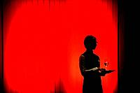 Silhouette of a waitress against a red wall