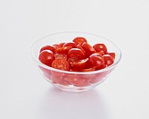 Whole and sliced cherry tomatoes in glass bowl