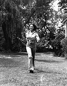 Young woman walking in the grass