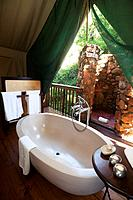 Large oval bathtub inside a luxury safari tent, Botlierskop Game Lodge, Mosselbay, South Africa.