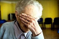 Portrait of a centennial woman in a elderly people home, hand covering her face.