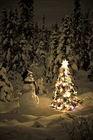 Snowman stands in a snowcovered spruce forest next to a decorated Christmas tree in wintertime