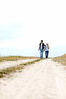 Full length of young hiking couple walking on path at field