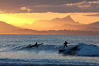 Surfersat sunset, The Pass, Byron Bay, New South Wales, Australia.
