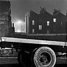 Lorry and terraced houses, Shoreditch, London, 1960-1965. The rear axle of a lorry in the foreground with the rear of terraced houses with windows lit...