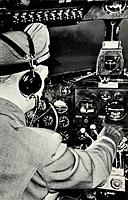 Pilot in the cockpit of a Douglas DC-3 aeroplane, 1940. View showing the pilot and part of the instrument panel of one of Chicago and Southern Airline...