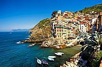 Photo of the colorful houses of the fishing port of Riomaggiore, Cinque Terre National Park, Liguria, Italy.