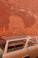 Car in fornt of red brick wall