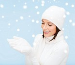 seasonal, people, happiness concept - smiling woman in winter clothes with something on palms