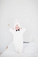Girl wearing rabbit costume standing on bed
