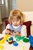 young three year old girl playing with play dough activity.