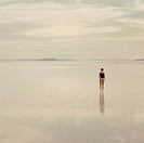 Woman standing on the flooded Bonneville Salt Flats, at dusk.