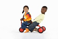 Two young children riding a tricycle together