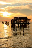 Silhouette of old wooden jetty at sunrise