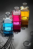 Cyan, magenta, yellow liquids in bottles on water and black background, and a close up of water droplets splashing.