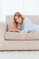 A woman lying on a couch is leaning on her elbows