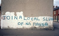 Graffiti on a wall in Northern Ireland, reading: Join a Local Slua of Na Fianna. Na Fianna was and is a republican youth movement, and a slua is a uni...