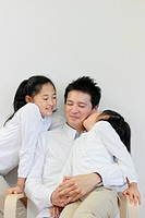 Father with Two Daughters, One Daughter Kissing Him on Cheek