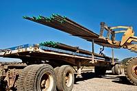 Loading drill pipe in oil-gas well area in Colorado.
