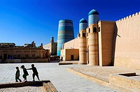 Children playing near the Kuhna Ark fortress and the unfinished minaret Kalta Minor. Uzbekistan, Khorezm, Khiva, Itchan Kala (inner town).