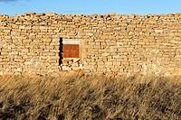 Stone wall with a rusty iron door. Pozondon, Teruel, Spain