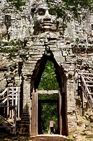 Old man passing through Angkor Thom west gate with his bicycle in Angkor Cambodia.