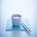 Sake in a cup next to a pair of chopsticks