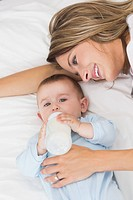 Baby boy drinking milk while lying by mother