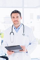 Confident male doctor with clipboard in hospital