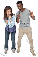 Portrait of a young couple singing into microphones