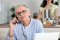 Elderly woman chatting on the phone whilst young helper works in the kitchen